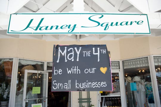 """""""The feeling is liberating,"""" said Harbor Wear owner Jen Stevenson, who made a sign in support of the reopening of non-essential retail stores for the shops at Haney Square on Monday, May 4, 2020, in downtown Stuart."""