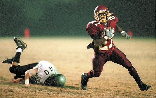 Tulare Union's Dominique Dorsey makes a quick move to the outside leaving Stockdale's Jacob Garnett on the ground during a play in the third quarter at Bob Mathias Stadium in 1999.