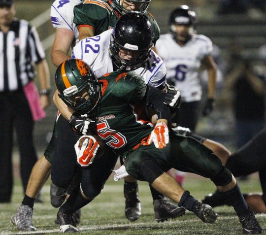 Porterville's Isaiah Jones (5) fights for yardage against Mission Oak' s Richard Torrez in a 2015 East Yosemite League game in Porterville. Jones rushed for 302 yards and six touchdowns in the Panther's 61-35 win.