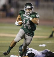 Michael Wright of Dinuba gains extra yardage at Dinuba High School in 2014.