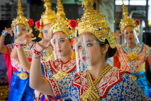 Traditional Thai dancers wearing protective face shields perform at the Erawan Shrine, which was reopened after the Thai government relaxed measures to combat the spread of the COVID-19 novel coronavirus, in Bangkok on May 4, 2020.  Thailand began easing restrictions related to the COVID-19 novel coronavirus on May 3 by allowing various businesses to reopen, but warned that the stricter measures would be reimposed should cases increase again.