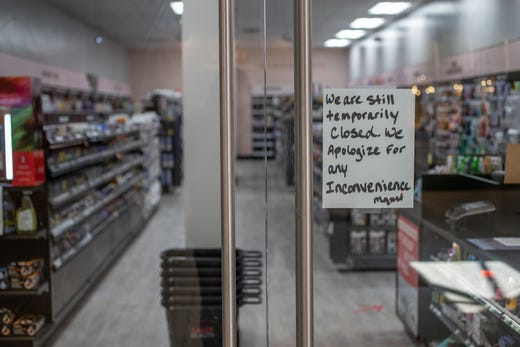 A sign in a store window at Greenwood Park Mall in Greenwood, Ind., lets customers know they are still temporarily closed on Monday, May 4, 2020.