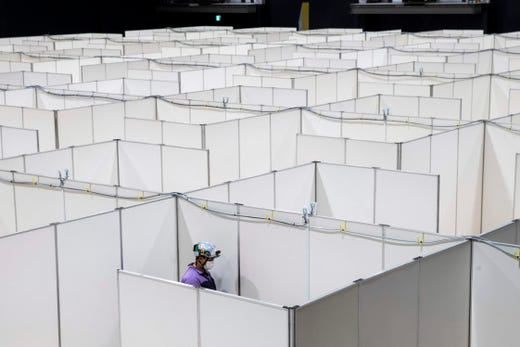 An employee works to set up a medical facility to accomodate COVID-19 patients with mild symptoms at the Nippon Foundation Para Arena in Tokyo on May 4, 2020.  Japan's government prepared on May 4 to extend its nationwide state of emergency to the end of May as it braces for a lengthy battle against the coronavirus pandemic.