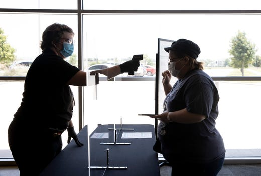 Lisa Ford, right, of Kyle, gets her temperature checked by Margaret Capulin before entering EVO Entertainment on Monday.  The movie theater in Kyle, Texas reopened Monday after Gov. Greg Abbott last week lifted the shelter in place order and allowed retail stores, restaurants and some other businesses to open to the public at no more than 25% capacity.