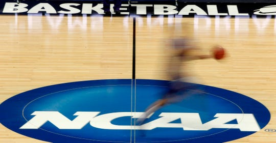 In this file photo, a player runs across the NCAA logo during practice in Pittsburgh.  (AP Photo/Keith Srakocic)