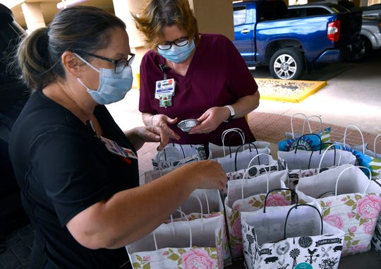 Nurses Kathy Gartman (left) and Leashia Ruelas look over the delivery of 200 small pies from Life of Pie to Abilene Regional Medical Center Tuesday. Community Foundation of Abilene pledged the delivery as part of Abilene Gives to thank healthcare workers.