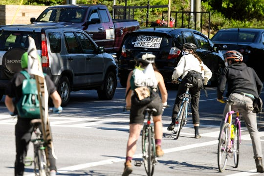 A group stops traffic to parade through Asheville in protest of paying rent amid job losses due to COVID-19 May 1, 2020.