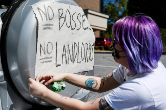 """Mary Bee tapes a sign onto the back of her car as a groups gathers to drive through Asheville in protest May 1, 2020. """"I'm worried about my fellow tenants who are out of a job,"""" said Bee, who was placed on paid leave amid COVID-19."""