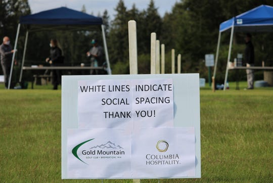 A sign directs golfers to maintain spacing at the check-in tents at Gold Mountain Golf Club on May 5, 2020.