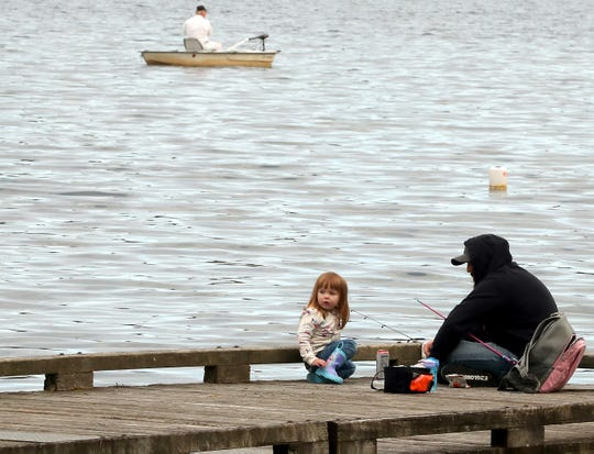 Scott Sear and daughter Haley, 2, fish from the dock at Kitsap Lake Park in Bremerton on Tuesday