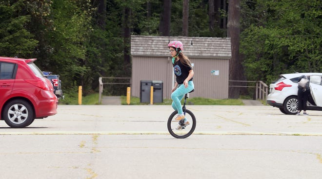 Violet Boeddeker, 11, rides her unicycle through the parking lot at South Kitsap Regional Park in Port Orchard on Tuesday. Violet and her sister Juliet were visiting the park with their mother Alexandra and using an empty portion of the parking lot for unicycling and rollerskating.