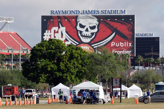 In this March 25 file photo, medical personnel test people for the coronavirus in the parking lot outside Raymond James Stadium, home of the Tampa Bay Buccaneers.