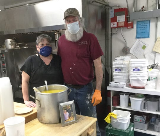 Sandy and Todd Heyman pose in the kitchen with a vat of fish chowder at Brewster-Pierce Memorial School in Huntington on Wednesday, April 29, 2020. The weekly free meal began as a monthly tribute to Edward Heyman, who died at age 27 in June 2016. Edward's photograph, dated April 20, 2026, leans against the pot.