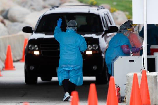 A medical worker directs a local resident at a drive-thru COVID-19 testing site in Waterloo, Iowa, on May 1. Local officials blame Tyson for endangering not only its workers and their relatives during the pandemic but everyone else who leaves home to work or get groceries.