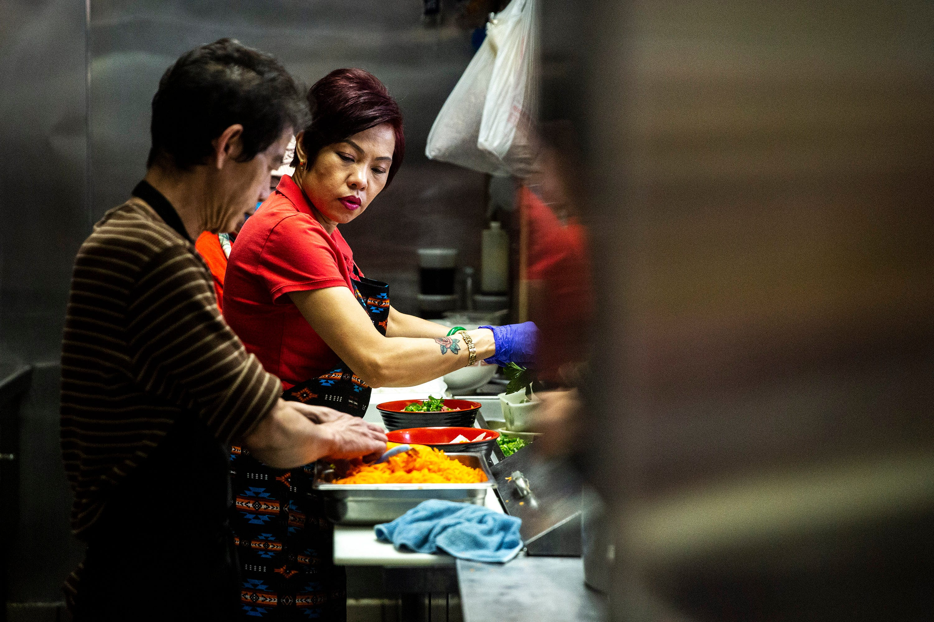 Brenda Tran, owner of the Vietnam Cafe, works in the kitchen with her staff to prep and prepare to-go orders May 3 in the Merle Hay Mall food court in Des Moines, Iowa.