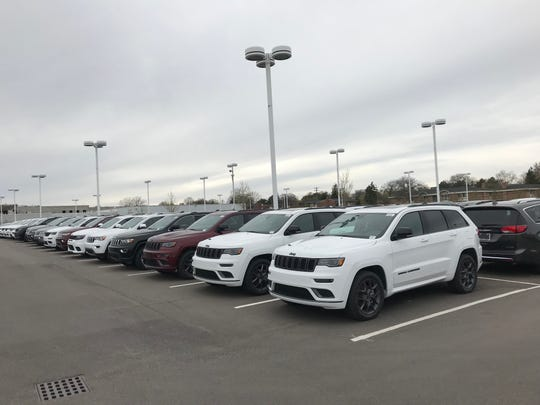 """Jeeps are parked on the lot at Suburban Chrysler Dodge Jeep Ram of Troy on May 5. Michigan auto dealerships have had to shut down sales floors as part of the """"Stay at Home"""" order in Michigan."""