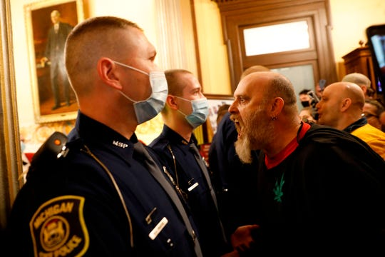 Protestors try to enter the Michigan House of Representative chamber and are being kept out by the Michigan State Police after the American Patriot Rally organized by Michigan United for Liberty protest for the reopening of businesses on the steps of the Michigan State Capitol in Lansing, Michigan on April 30, 2020. - The group is upset with Michigan Gov. Gretchen Whitmer's mandatory closure to curtail Covid-19.