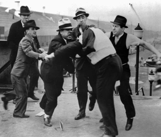 FILE - In this May 26, 1937 file photo, Richard Frankensteen, United Auto Workers organizational director, with coat pulled over his head, is pummeled by Ford Motor. Co. agents at the gate of the Ford River Rouge Complex in Dearborn, Mich. Ford security personnel were countering the UAW's efforts to organize employees at the factory complex.