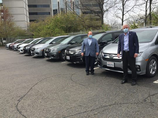 Mayor Mike Duggan and Honda executive Rick Schostek show off 10 Odyssey minivans the company modified to protect drivers as they transport Detroiters to the state fairgrounds for COVID-19 testing. Detroit is the first U.S. city to get the vehicles, which are modeled after a program Honda launched in Tokyo after the pandemic hit to keep taxi drivers safe from potential infection from passengers.