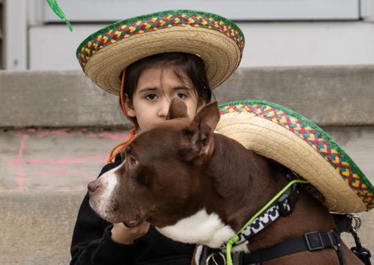 Camila Rick of Detroit holds her sombrero after taking a photo with her dog Diablo for her school's Spanish club outside of their house in Southwest Detroit on Tuesday, May 5, 2020,