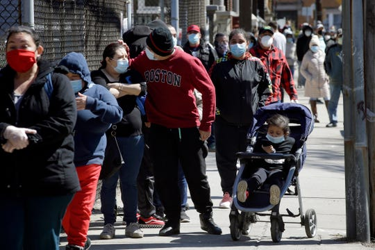 People wear masks out of concern for the coronavirus while standing in line outside a Salvation Army food pantry Tuesday in Chelsea, Mass.