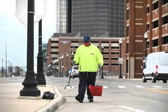 Robert Alexander of the Downtown Detroit Business Improvement Zone Ambassador team sweeps up debris on Detroit's east side this week. The Jefferson East nonprofit contracts with the organization through the Downtown Detroit Partnership for street cleaning.