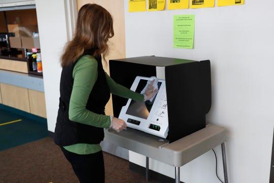 Warren City Clerk Sonja Djurovic Buffa sanitizes the ExpressVote machine at the Warren City Hall, Tuesday, May 5, 2020, in Warren.