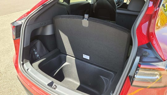 Sub-trunk storage in the Tesla Model Y may also be used for a rear-facing, third-row seat.