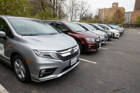 Ten donated 2020 Honda Odysseys sit in the parking lot of the Detroit Public Safety Headquarters in Detroit.