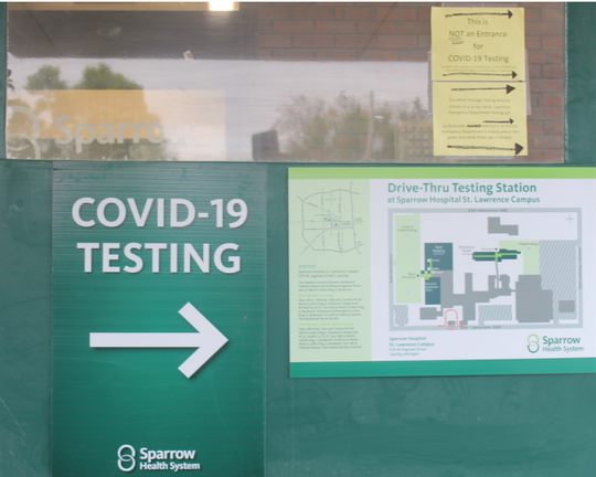 A sign points to a COVID-19 testing site at a Sparrow Health System facility in Lansing on Tuesday, May 5, 2020.