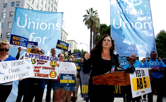 In this Aug. 28, 2019, file photo Assemblywoman Lorena Gonzalez, D-San Diego, speaks at rally calling for passage of her measure to limit when companies can label workers as independent contractors at the Capitol in Sacramento, Calif. California is suing ride-hailing companies Uber and Lyft, alleging they misclassified their drivers as independent contractors under the state's new labor law, AB5, that took effect Jan. 1.