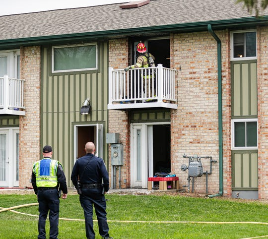 Two City of Fond du Lac Police officers watch Tuesday, May 5, 2020 as a Fond du Lac Fire/Rescue member looks over a burnt area where an apartment unit was on fire at 691 east Scott Street in Fond du Lac, Wis. Doug Raflik/USA TODAY NETWORK-Wisconsin