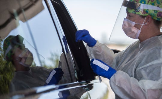 Stacy Brown, a registered nurse for Lee Health, administers a swab sample for coronavirus testing of a drive-thru patient, Friday, May 1, 2020 at the Page Field Mobile testing facility.