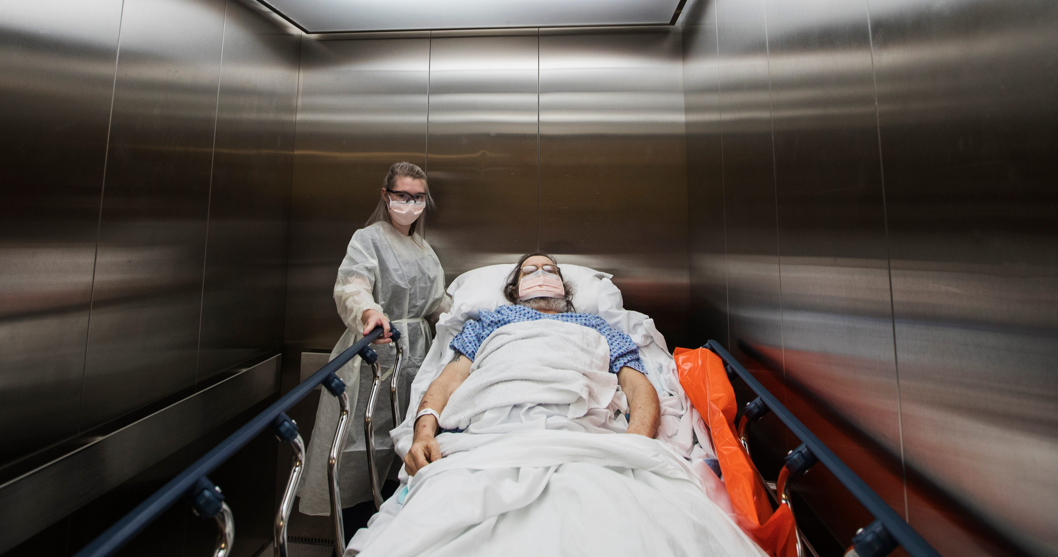 Maddie Dalby, 20, a transporter at Gulf Coast Medical Center, maneuvers a patient in an elevator as they make their way back to his designated room, Wednesday, April 29, 2020.