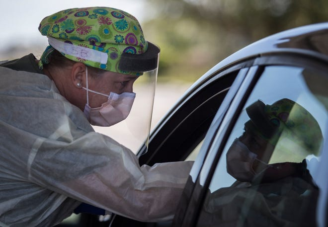 Stacy Brown, a registered nurse for Lee Health, administers a swab sample for coronavirus testing of a drive-thru patient at the Page Field Mobile testing facility.