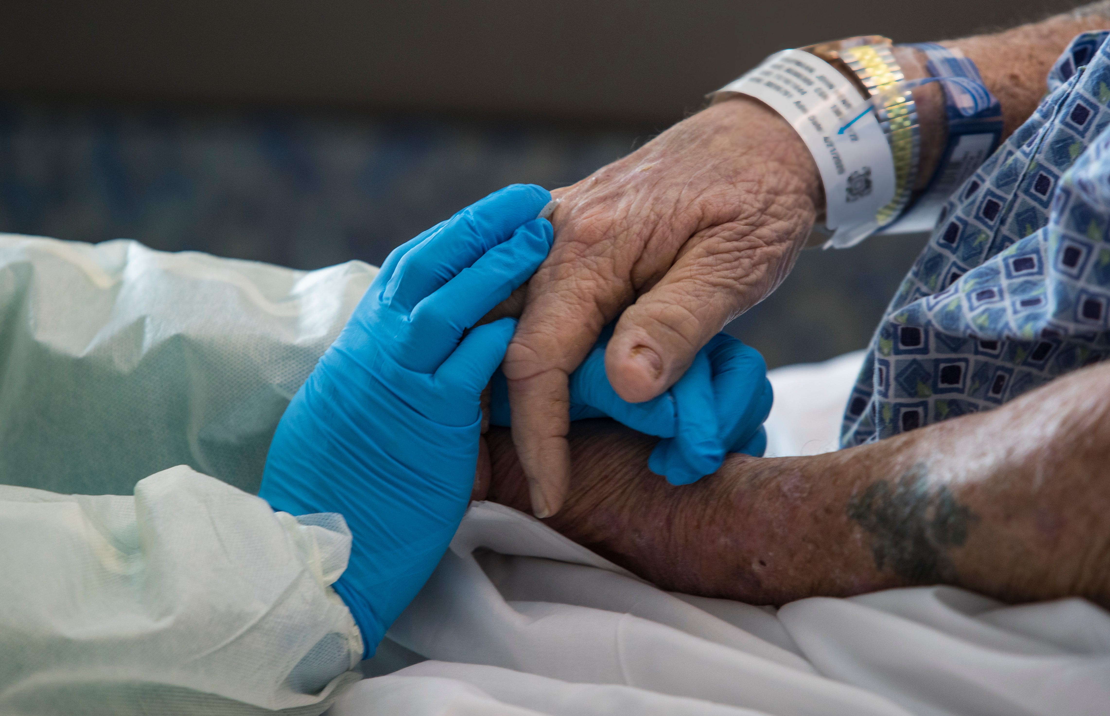"""John Henry Kaufmann, a patient who after showing symptoms similar to COVID-19 tested negative, shows his gratitude towards primary care nurse Sherri Parmar by gently grasping her hands during a tearful and emotional exchange Wednesday April 29, 2020. """"She always gives me the courage to bounce back. And I have,"""" Kaufmann said."""