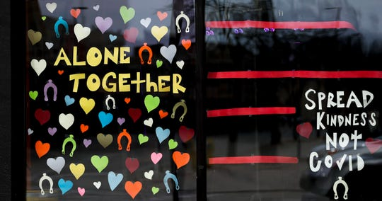"""""""Alone together, spread kindness not COVID,"""" is displayed Tuesday at Black Saddle in downtown Green Bay."""