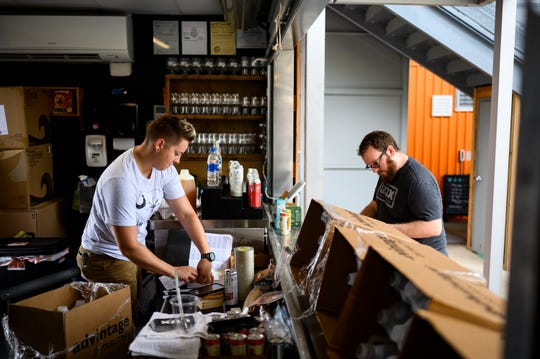 Greenville Beer Exchange owner Devin Cox, right, and beer tender Kala Schultz, prepare for customers at their Gather GVL location May 5, 2020.