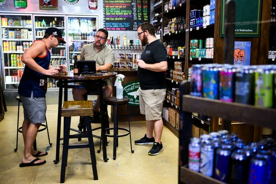 Greenville Beer exchange owner Devin Cox, right, and manager Evan Fatula, left, look at a list of available beers to purchase from distributor Steve Haden Monday May 4, 2020.