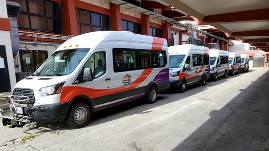 Commonwealth Office of Transit Authority vehicles await incoming passengers from the United flight arriving from Guam at the Saipan International Airport on May 2.