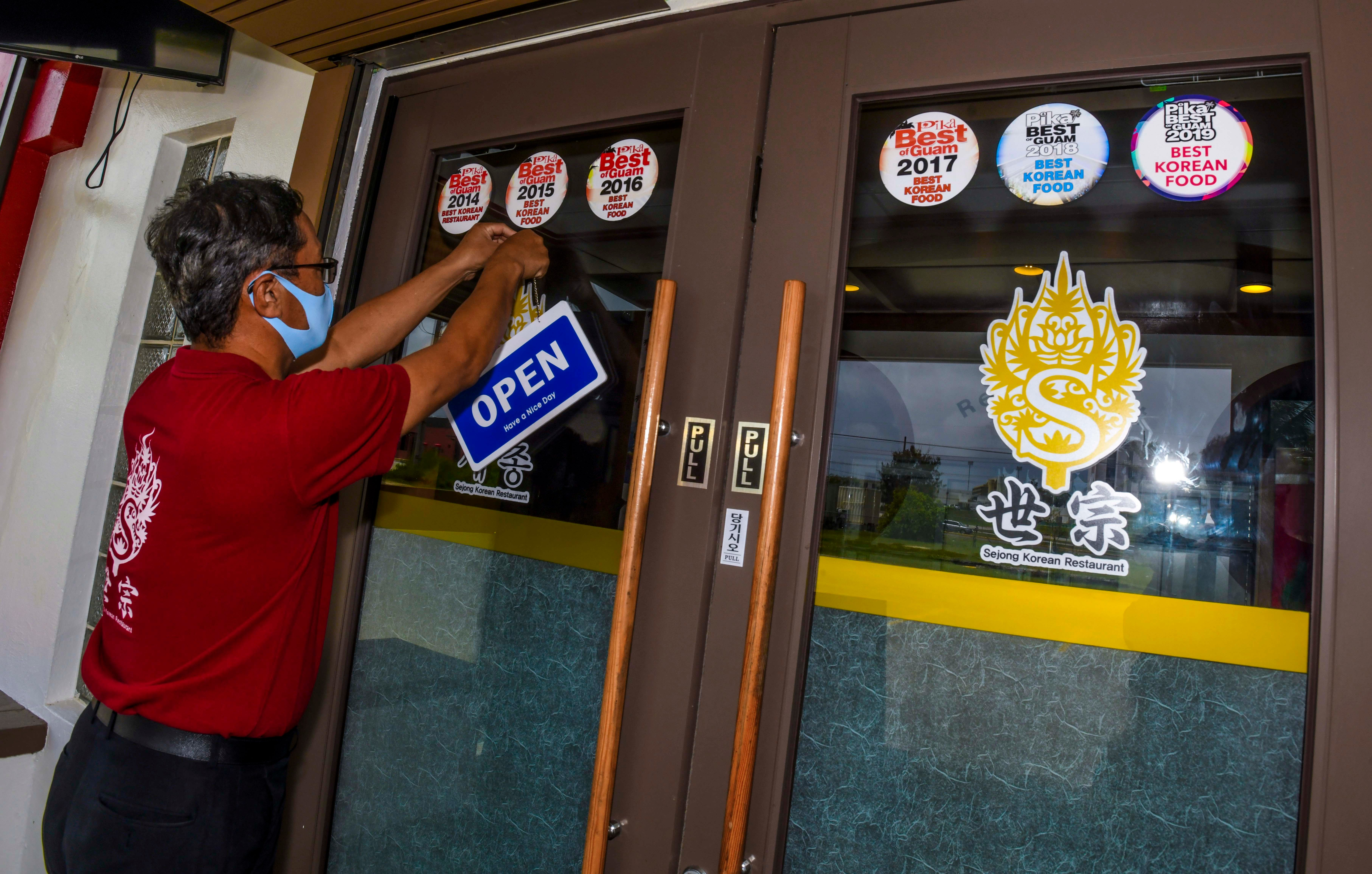 General Manager Alex Baik hangs an open sign at the entrance of the Sejong Korean Restaurant in Tamuning in this May 5 file photo as the restaurant reopened to serve lunch and dinner take-out orders. The reopening of restaurant dine-in services will be postponedafter 11 COVID-19 cases were confirmed Wednesday night.