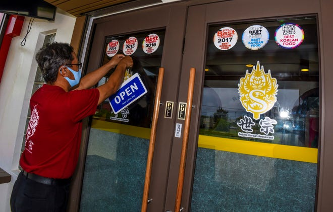 General Manager Alex Baik hangs an open sign at the entrance of the Sejong Korean Restaurant in Tamuning in this May 5 file photo as the restaurant reopened to serve lunch and dinner take-out orders. The reopening of restaurant dine-in services will be postponed after 11 COVID-19 cases were confirmed Wednesday night.