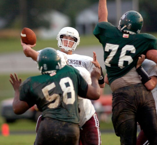 Henderson County quarterback Will Fidler drops back for to pass under pressure from North's Jordan Lewis, left, and Matt Hawkins at Central Stadium on Aug. 26, 2005.