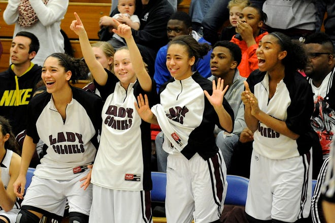 Members of the Henderson County Lady Colonels basketball team, from left, MiKayla Gilbert, Alysia Jacobs, Breanna Chester and Alisha Owens, celebrate as it becomes apparent they will win the 2013 regional championship game at Caldwell County High School.