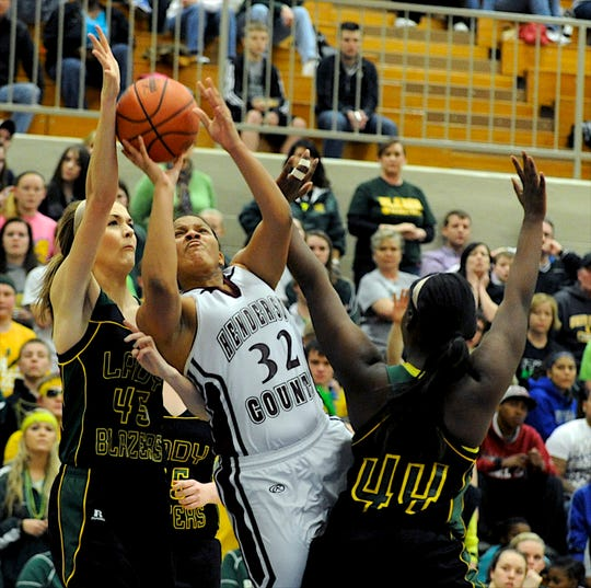 Henderson County's Brooke Tapp, center, draws the foul from UHA's Meg Starling, left, during the 2013 Second Region championship game in Princeton.