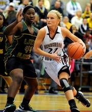 Henderson County's Ellie Fruit, right, drives to the basket around UHA's Cache Richardson during the 2013 regional championship game at Caldwell County High School.
