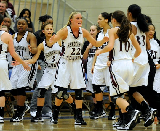 Henderson County's Ellie Fruit, center, encourages her teammates as they huddle up during a timeout while playing UHA in the 2013 regional championship at Caldwell County High School.