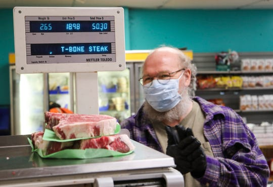 Mack Thompson rubs his gloves hands in anticipation as his steak is weighed at Kingsley Meat on Tuesday afternoon. It was Thompson's first steak in eight weeks since the coronavirus outbreak shut down most of Kentucky.