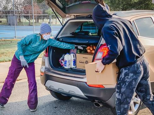 Volunteers load a driver's car at a food pantry.