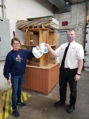 Piggly Wiggly manager Rob Ullman and TREP's Lynn Skarvan toast milk donation.